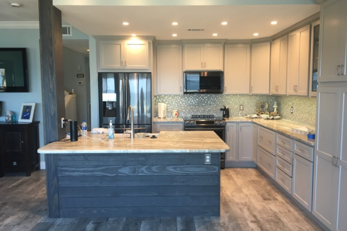 beautiful kitchen with Fantasy Brown countertops, seafoam green/steel backsplash, wood look tile floor, pewter shaker-style cabinets, and grey shiplap on island