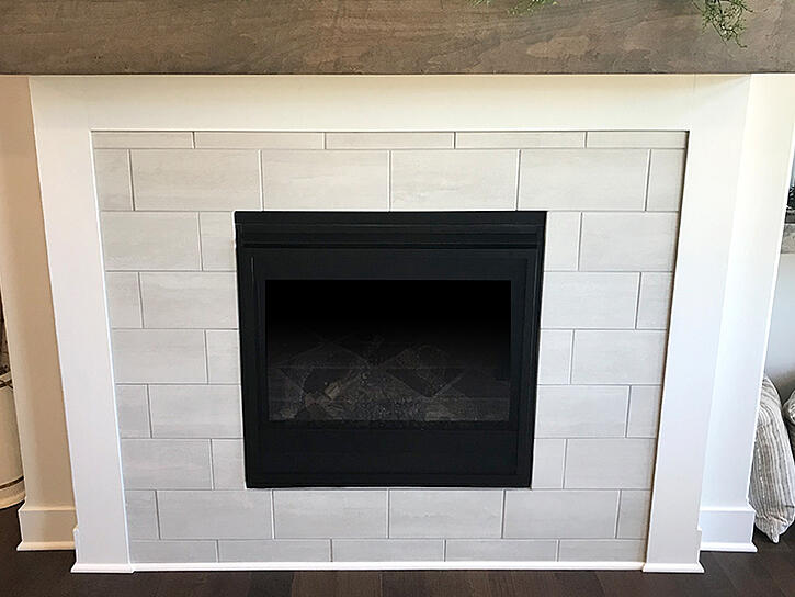 Clean, elegant fireplace with large white tile surround