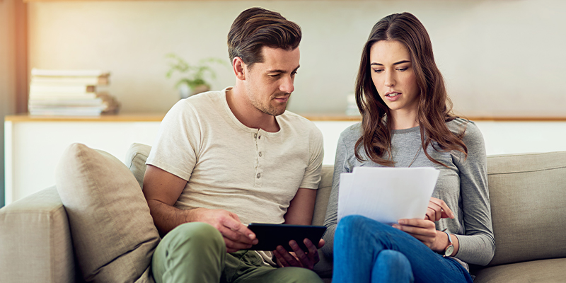 Young couple on a couch doing research