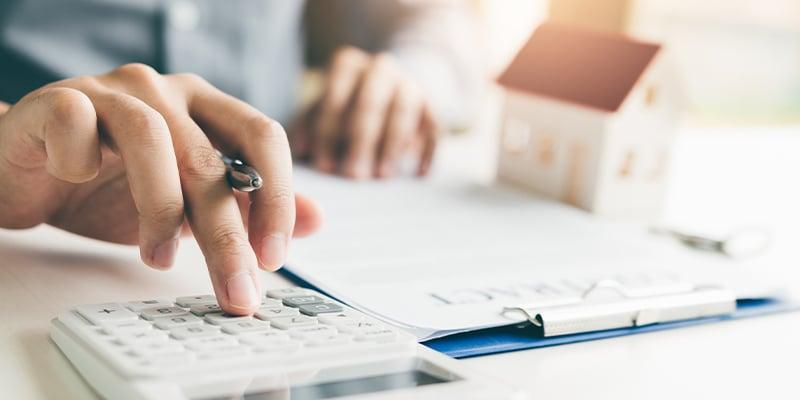 Person using a calculator to prepare home budget