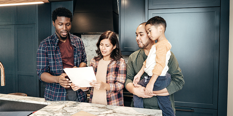 Family looking over kitchen floor plans with contractor